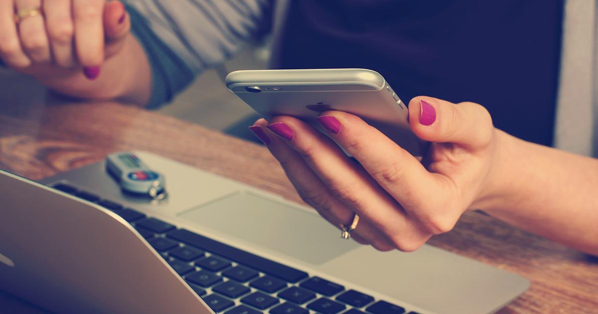 Frau mit Smartphone am Handy und vor dem Laptop