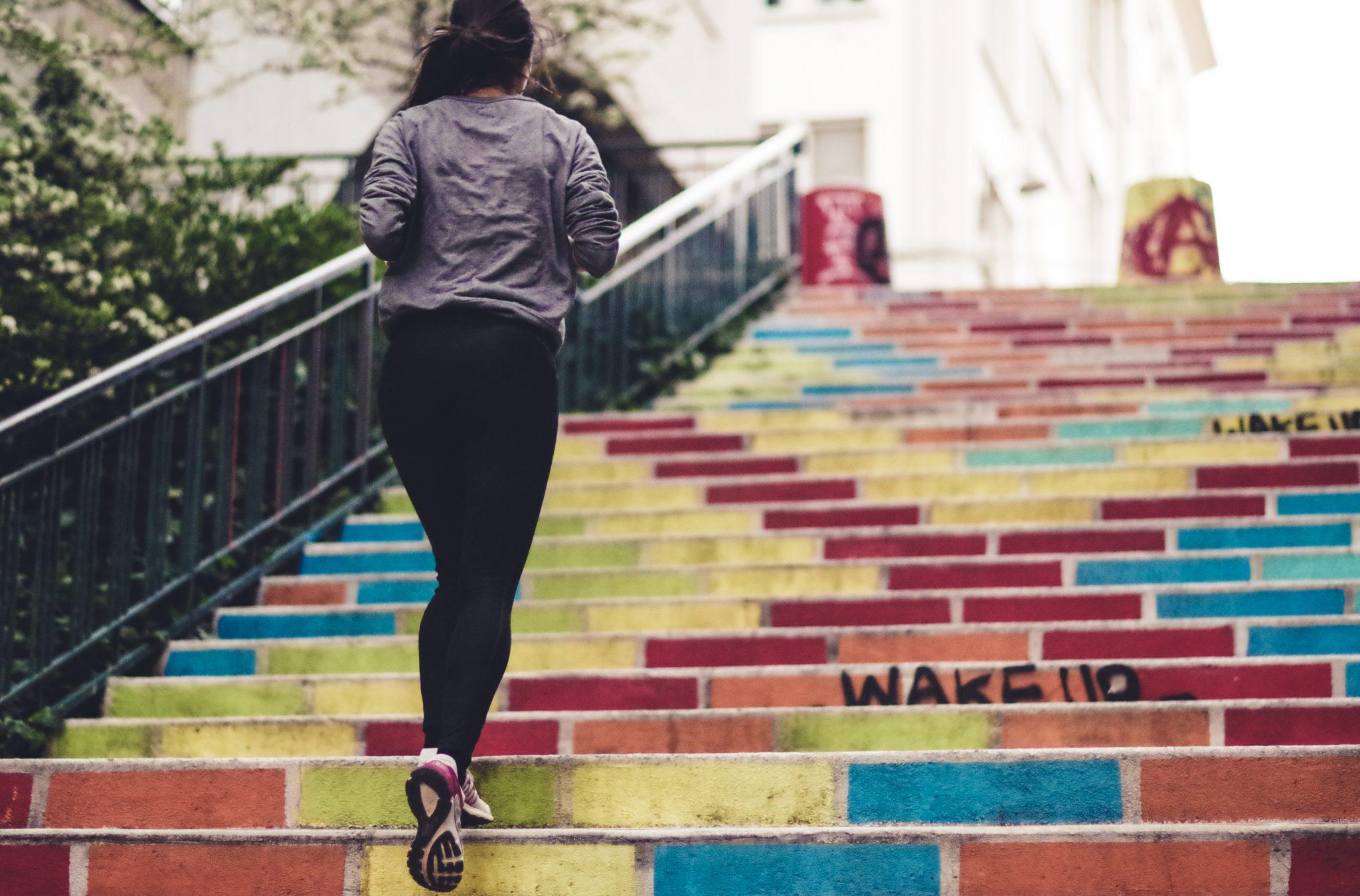 Frau die Treppen hoch joggt