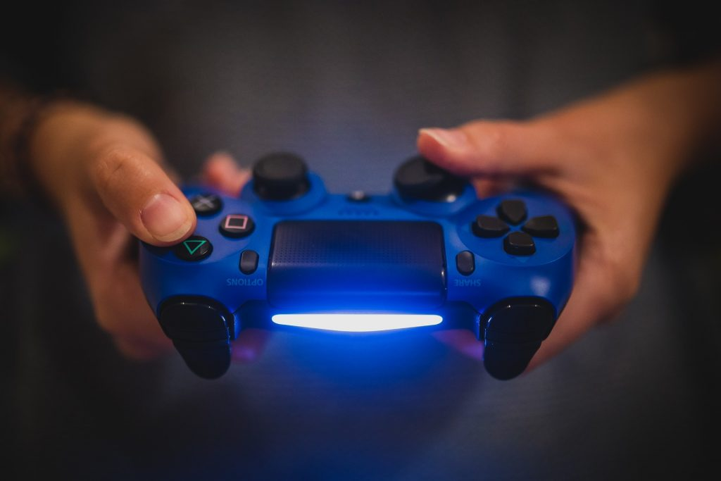 Personal hält Play-Station-Controller in der Hand
