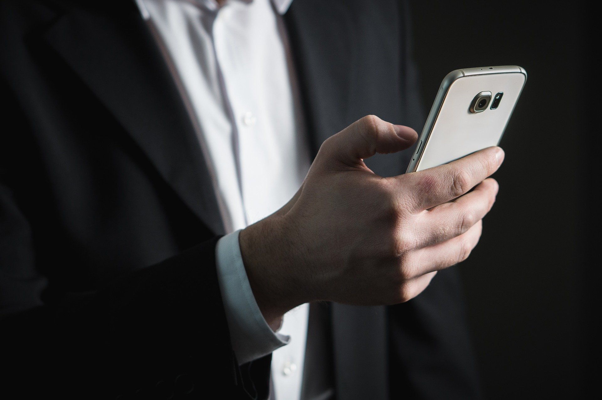 Mann im Anzug hält Smartphone in der Hand