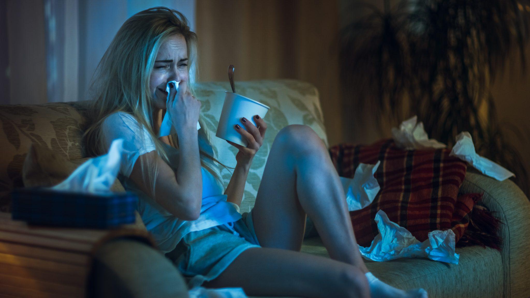 Eine blonde Frau, die heulend auf dem Sofa sitzt und einen Eisbecher in der Hand hält.