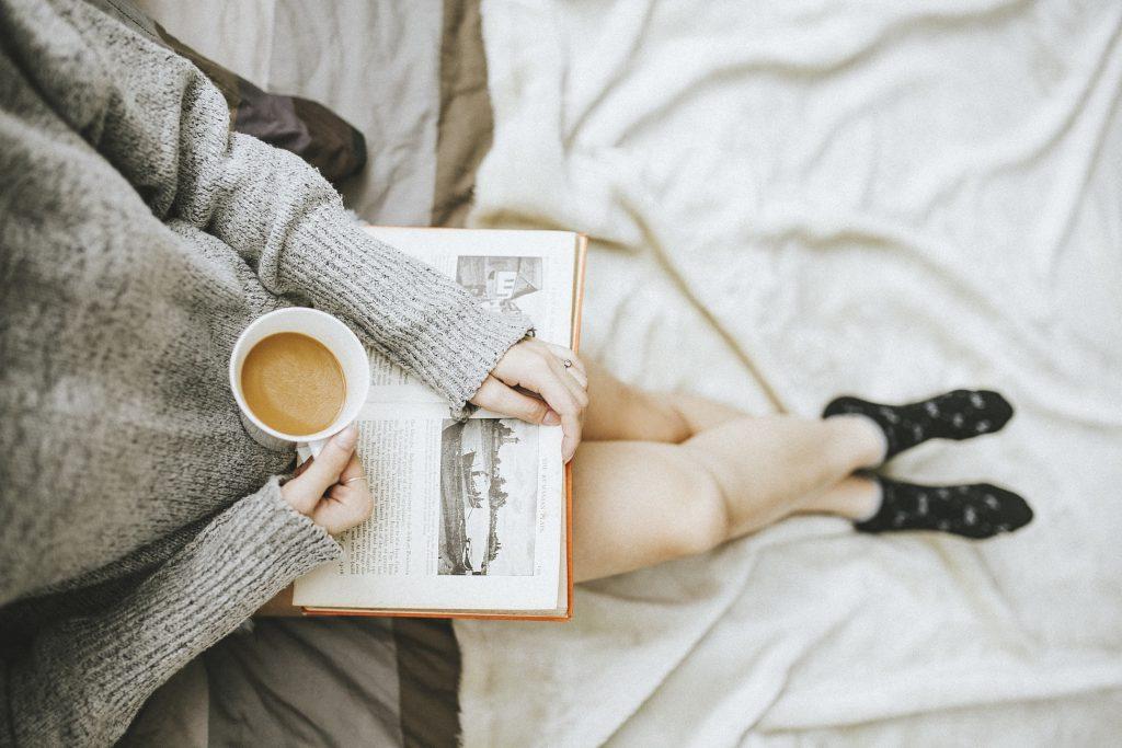 Eine Frau, die eine Tasse Kaffee in der Hand hält und ein Buch liest.
