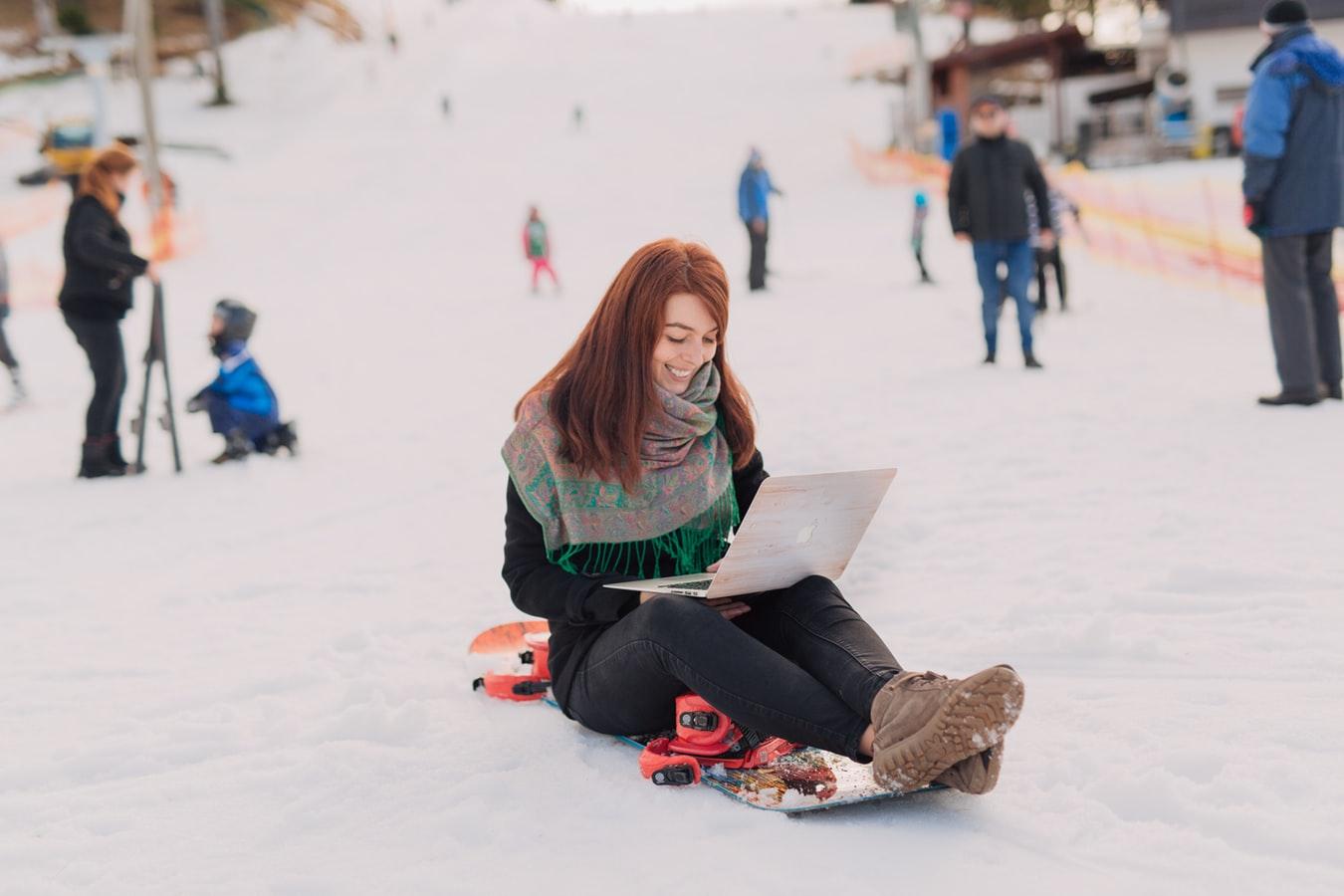 Frau sitzt im Schnee und guckt auf einen Laptop.
