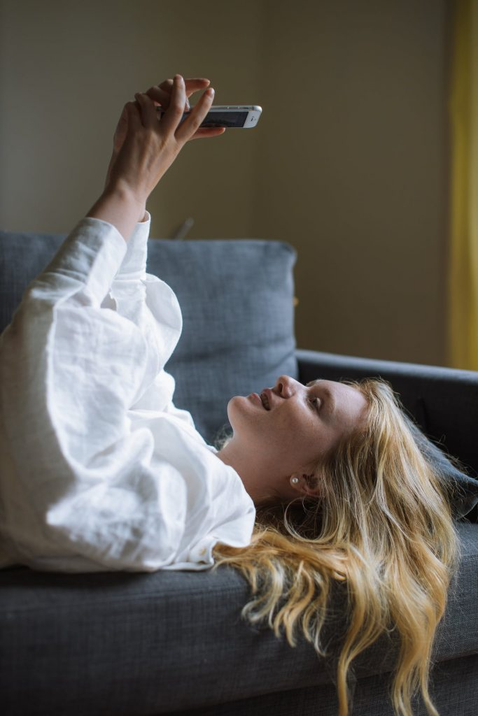 Frau liegt auf dem Sofa schaut aufs Handy
